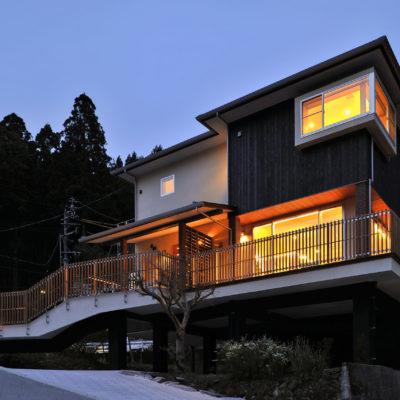 土地の傾斜を利用した設計のデッキの上に建つ家